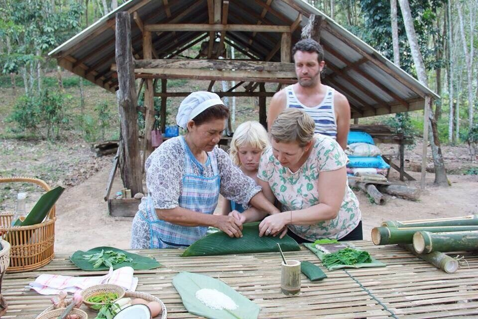 Father, mother and daughter learning how to prepare rice for Khao Sok jungle cooking in bamboo.